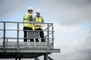 Two men at a wastewater treatment plant discussing process, auditing and sampling